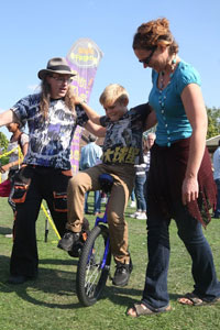 parent helping child on unicycle